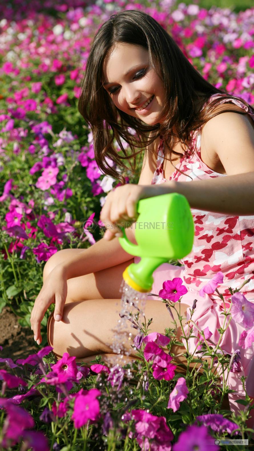 Dívka zalévá květiny.