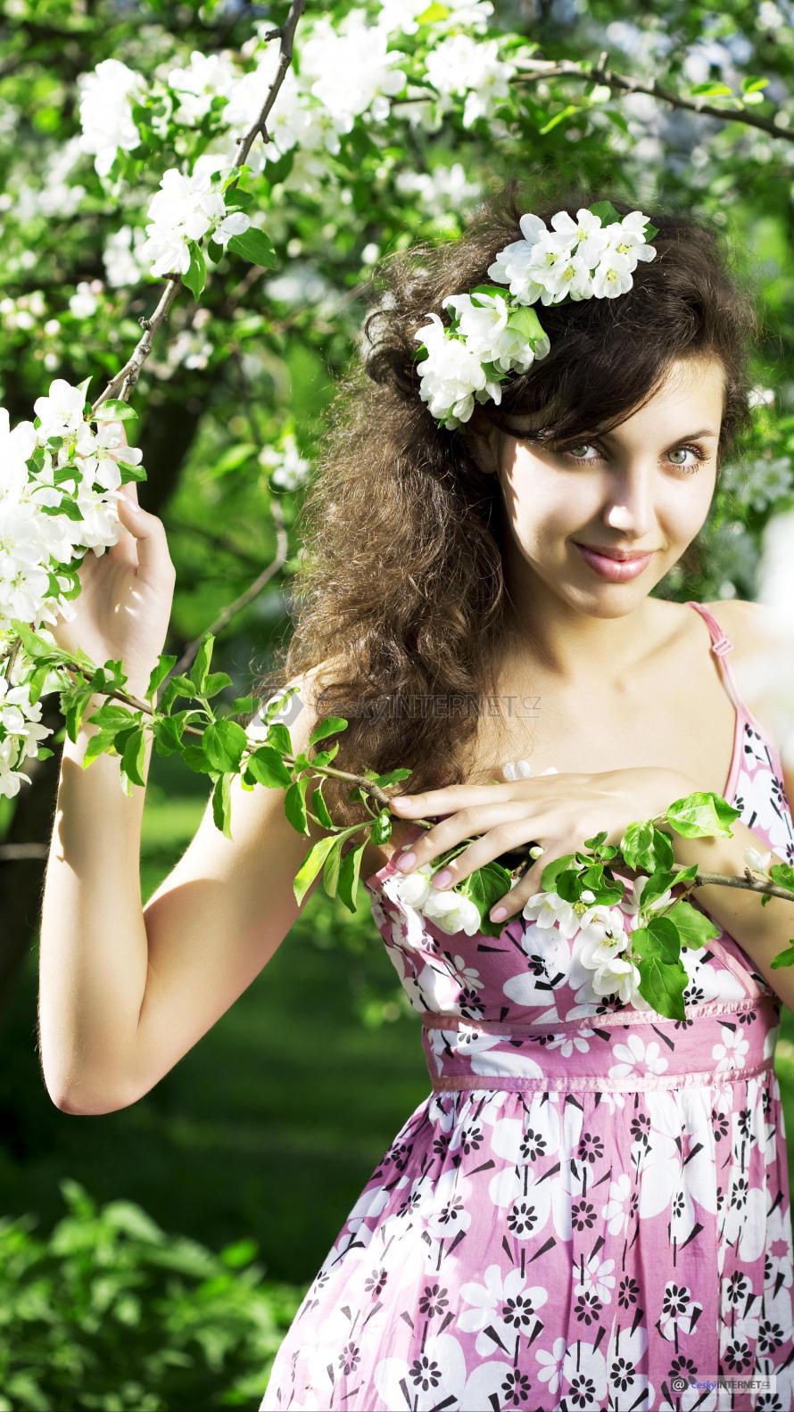Dívka se fotí s květy jabloně.