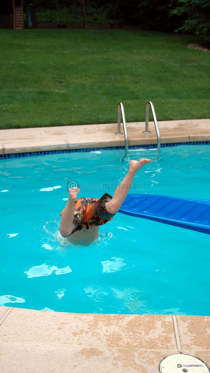 Chlapec skákající šipku do bazénu.