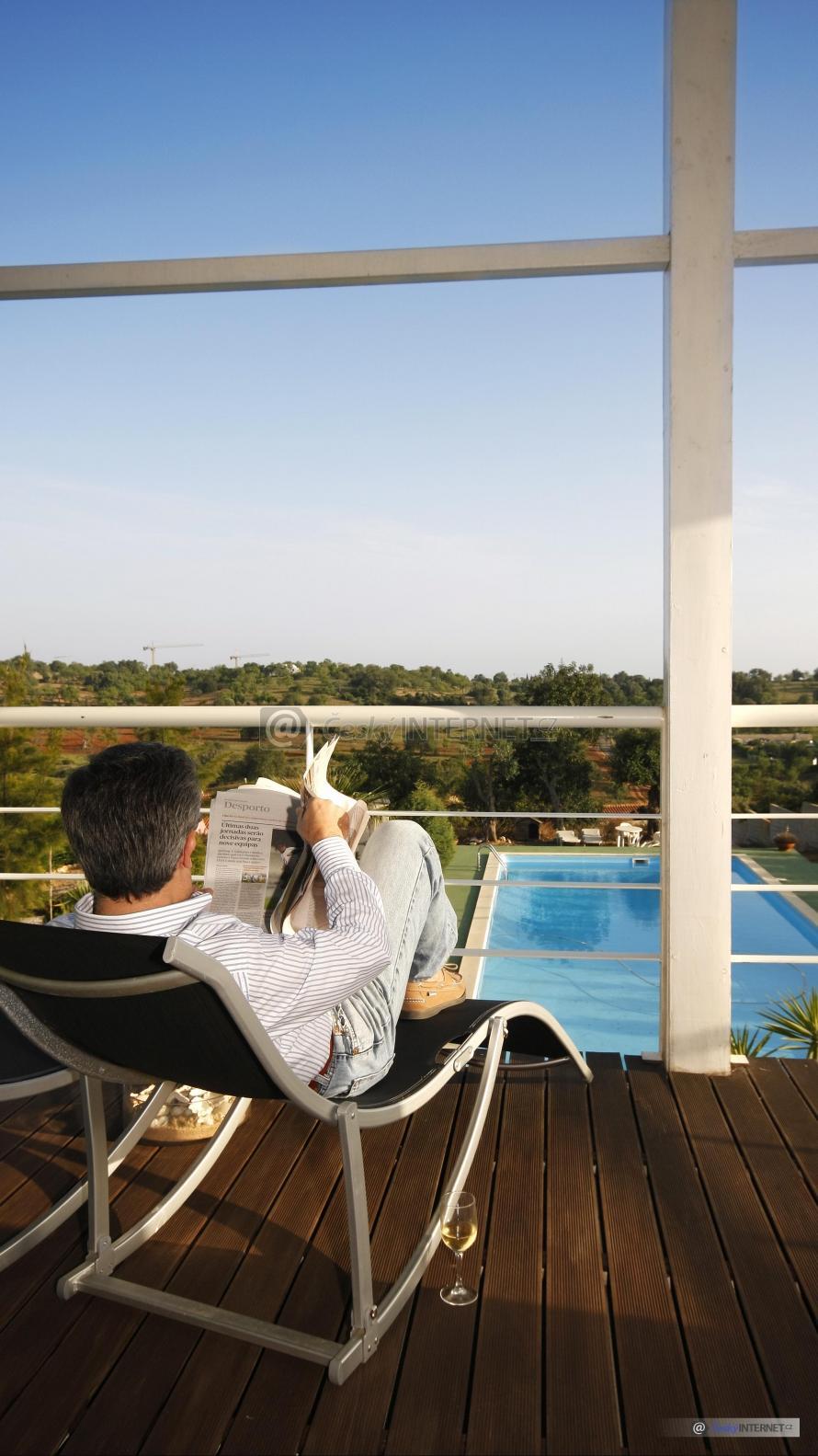 Muž relaxující na lehátku s výhledem na zahradu s bazénem.