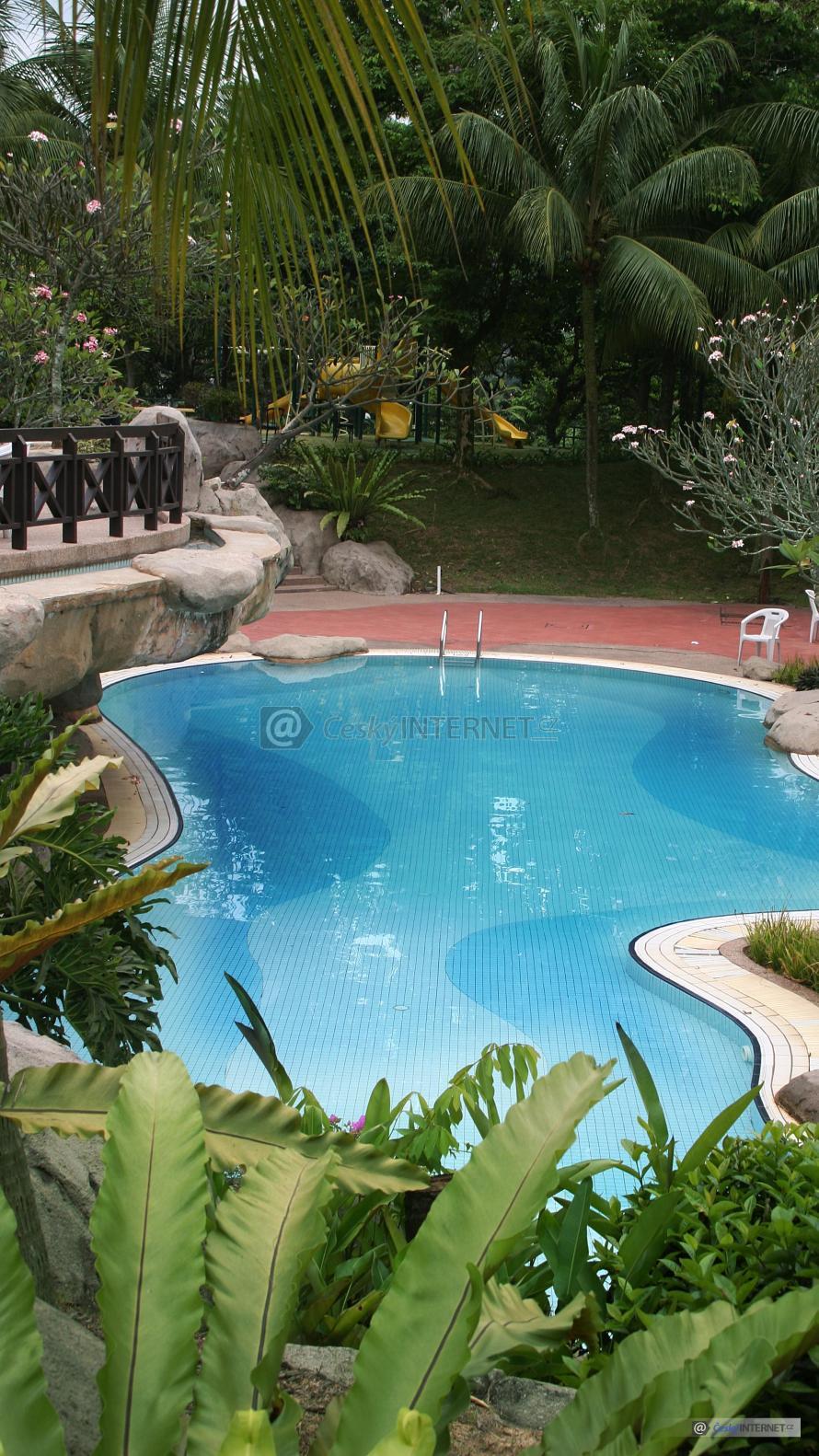 Bazén v rozkvetlé zahradě s terasou.