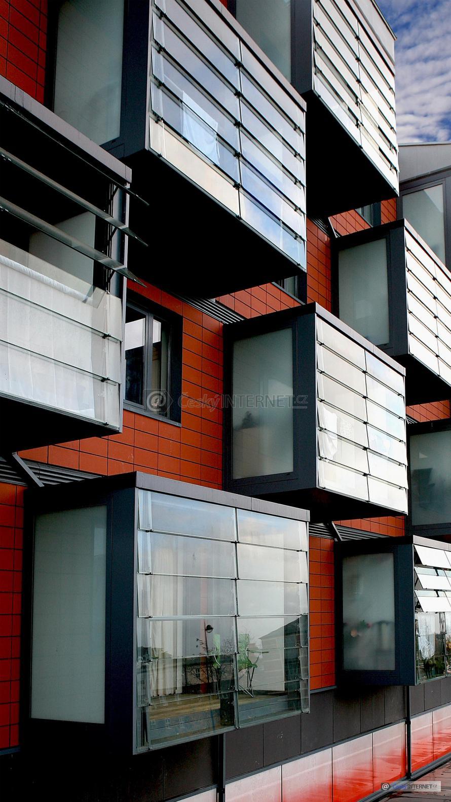 Moderní bytový dům s prosklenými lodžiemi.