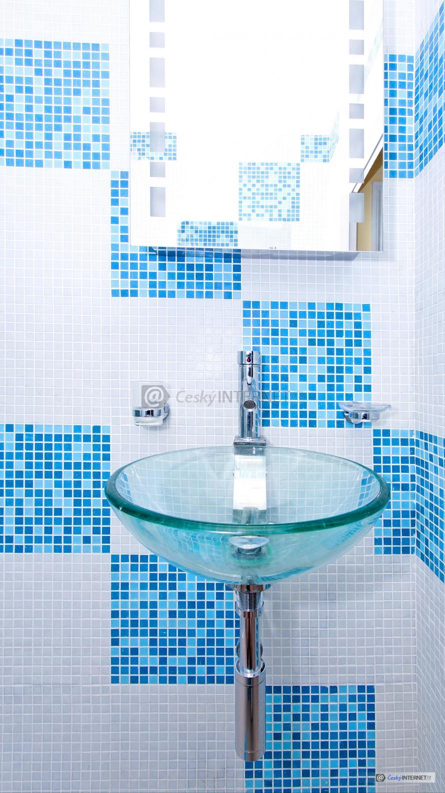 Detail rohu koupelny s umyvadlem a zrcadlem.