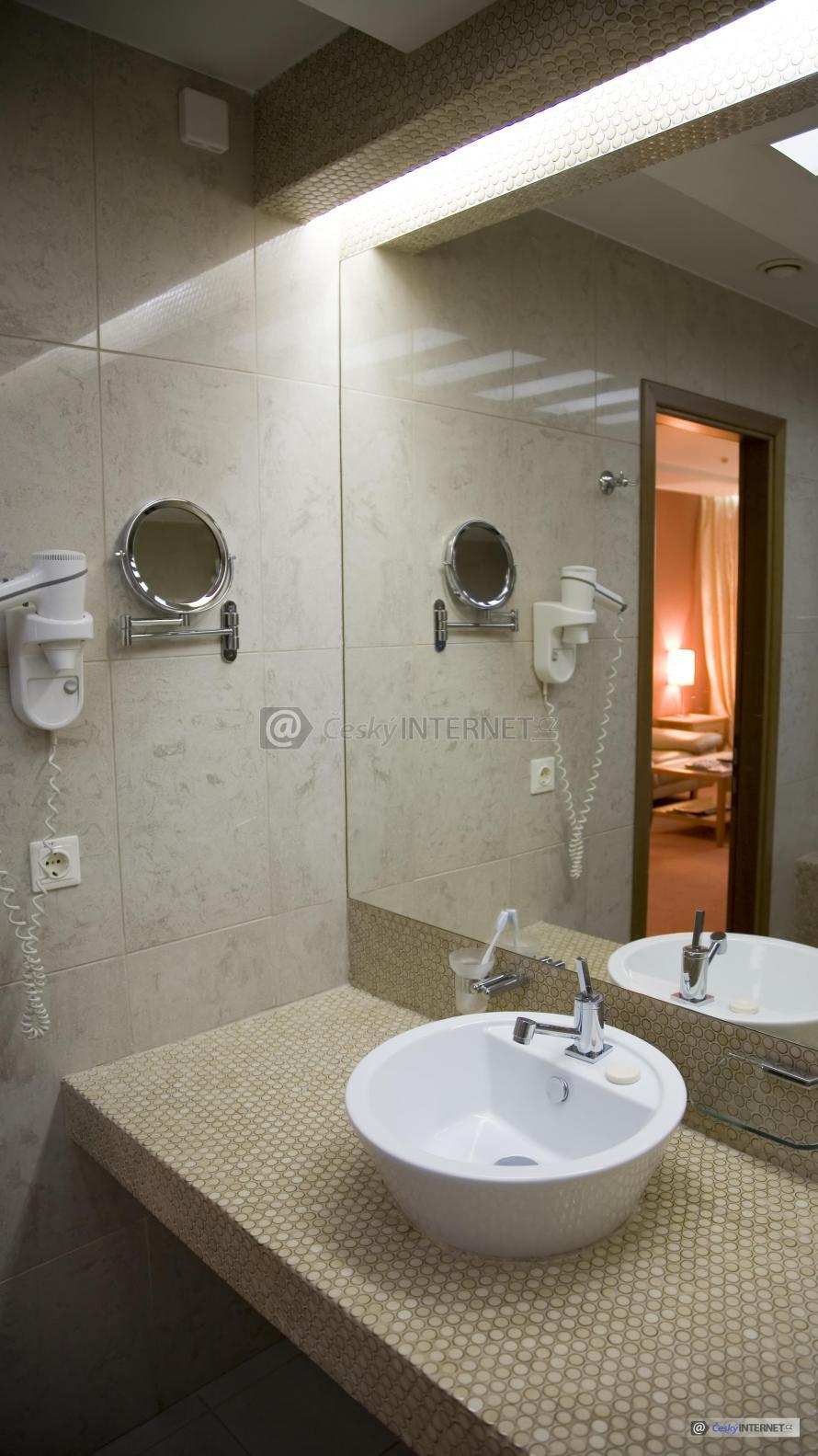 Detail koupelnového zrcadla a umyvadla s baterií.