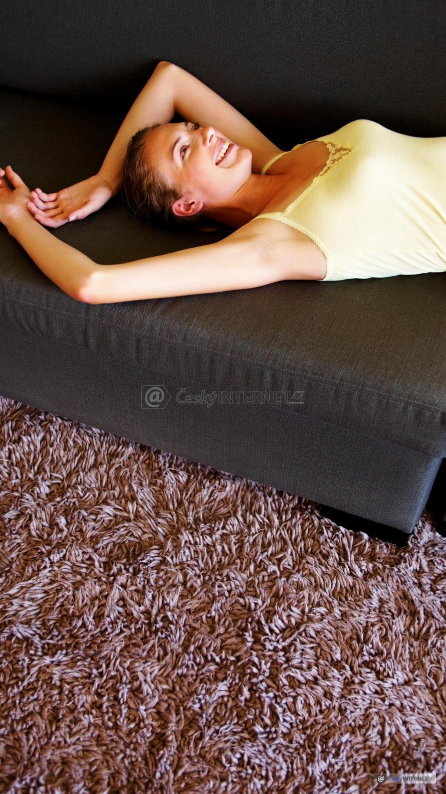 Dívka leží na čalounění sedací soupravě.