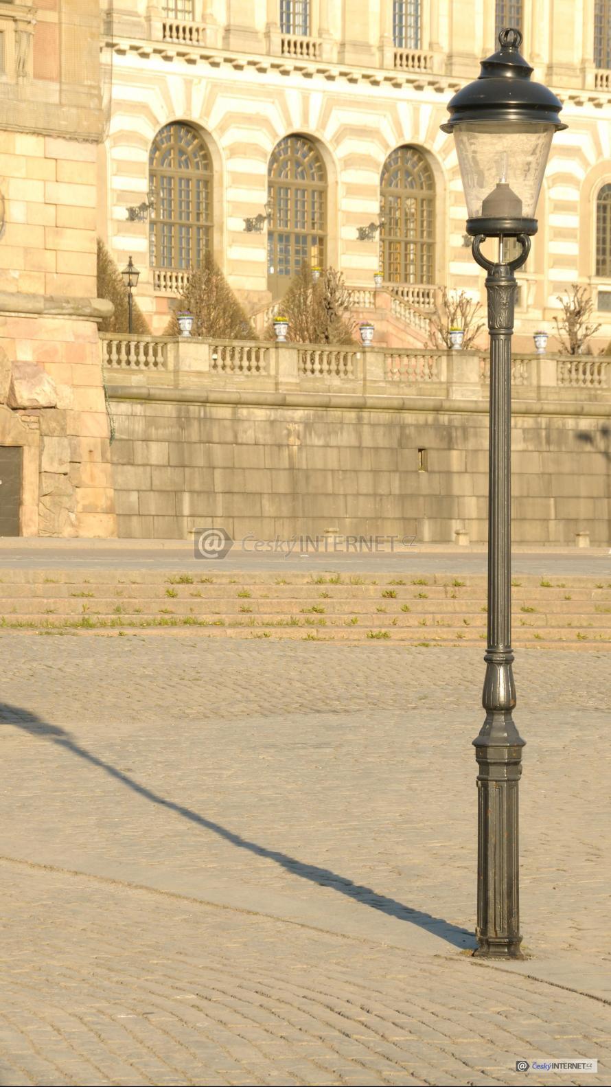 Lampa na chodníku před historickou stavbou, kamenná dlažba.