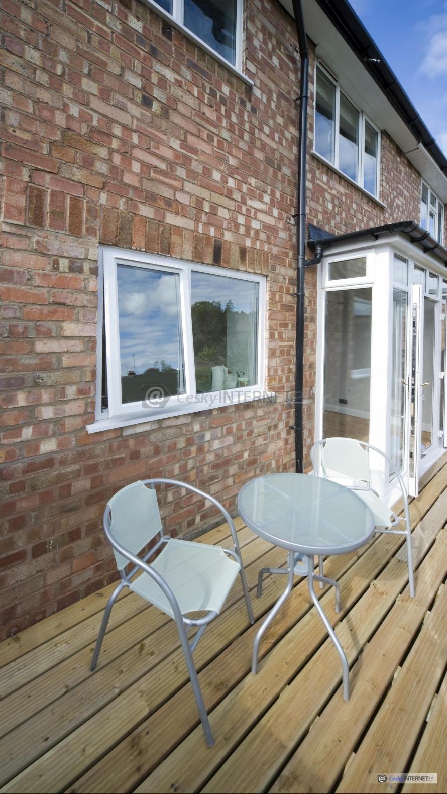 Stolek s židlemi na dřevěné terase u domu.