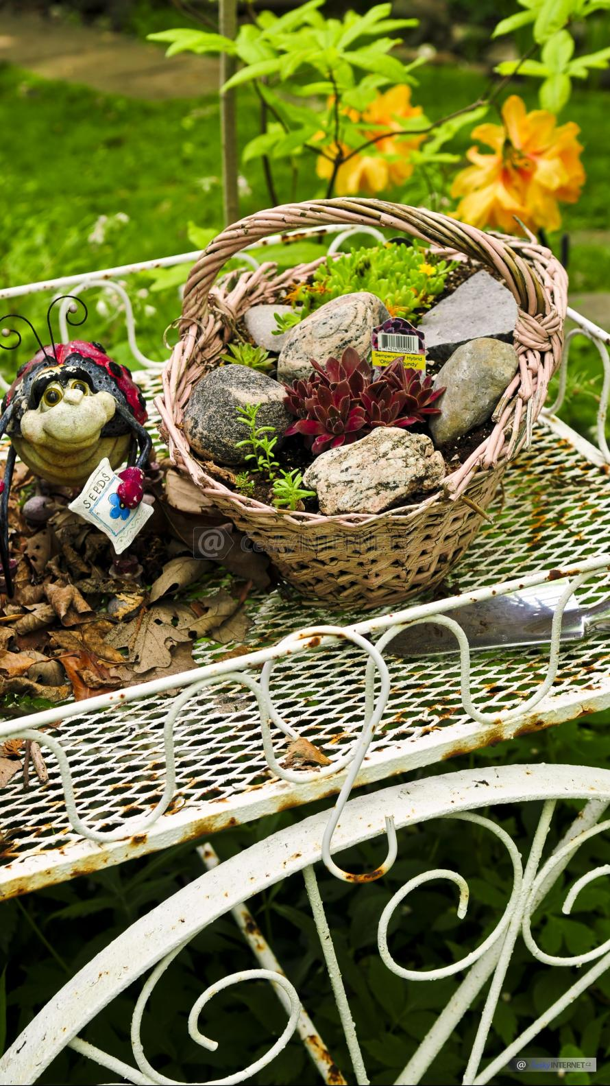 Aranž v okrasné zahradě, košík s rostlinami na kovovém nábytku.