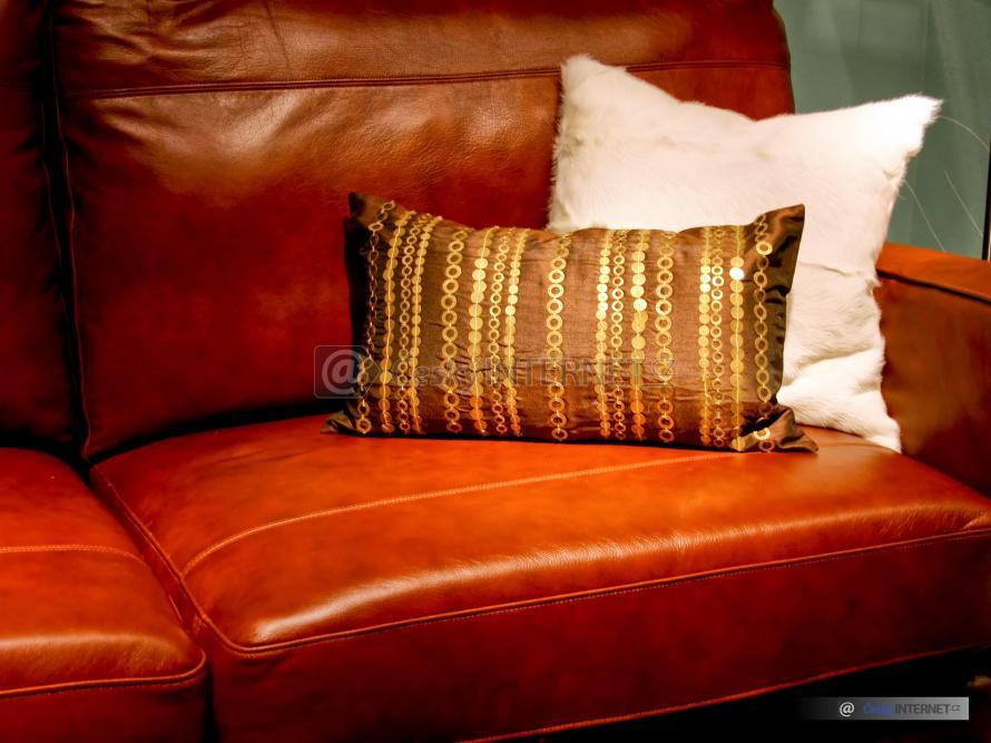 Cihlová kožená sedací souprava s polštáři - detail, osvětlení solitéru v interiéru. Atmosféra.