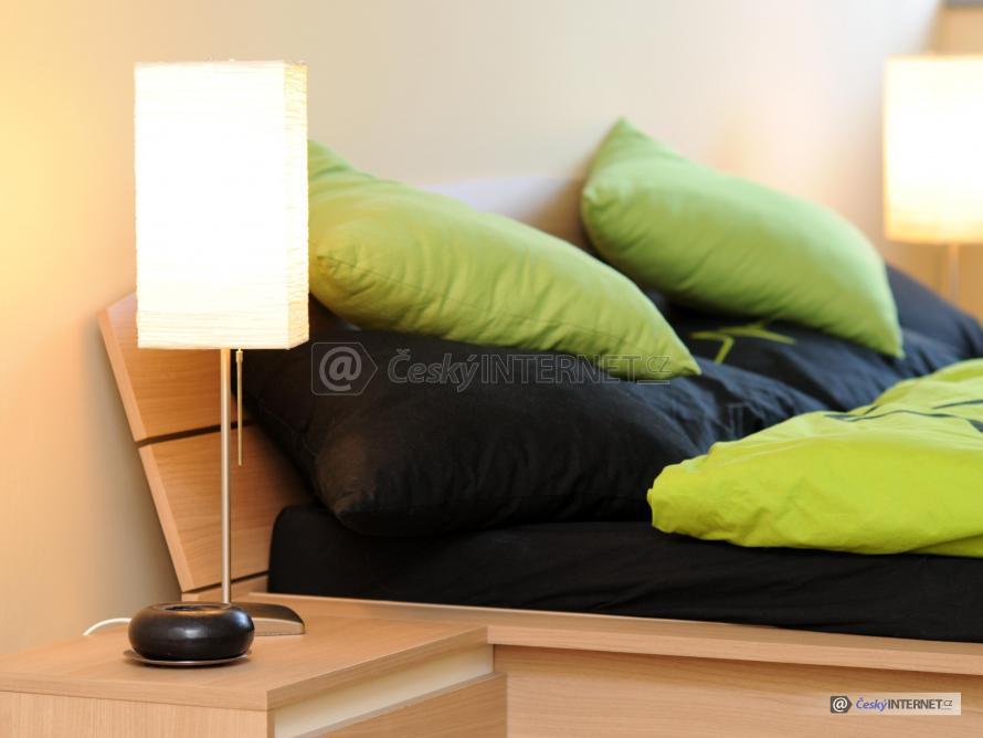 Detail na postel s polštáři a peřinou, noční stolky se stolními stojacími lampami.