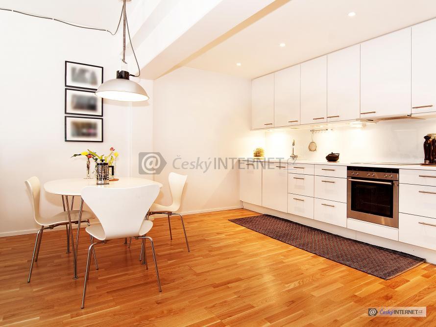 Moderní prostorná kuchyně s jidelním stolem.