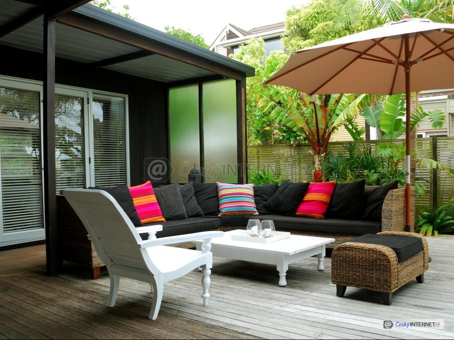 Ratanová sedací souprava na dřevěné terase u domu.