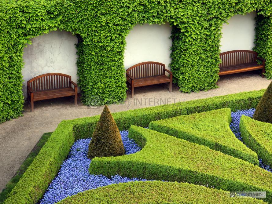 Okrasná zahrada s lavičkami.