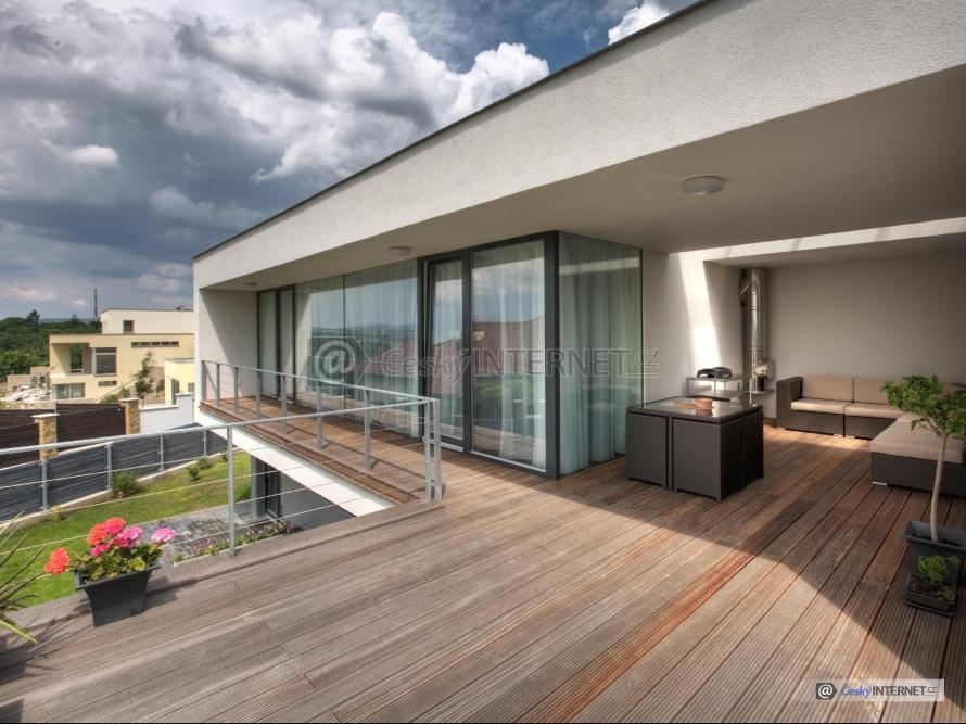 Dřevěná terasa s ratanovým nábytkem.