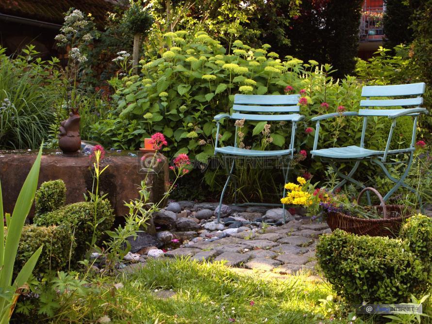 Detail okrasné zahrady, zahradní křesla.