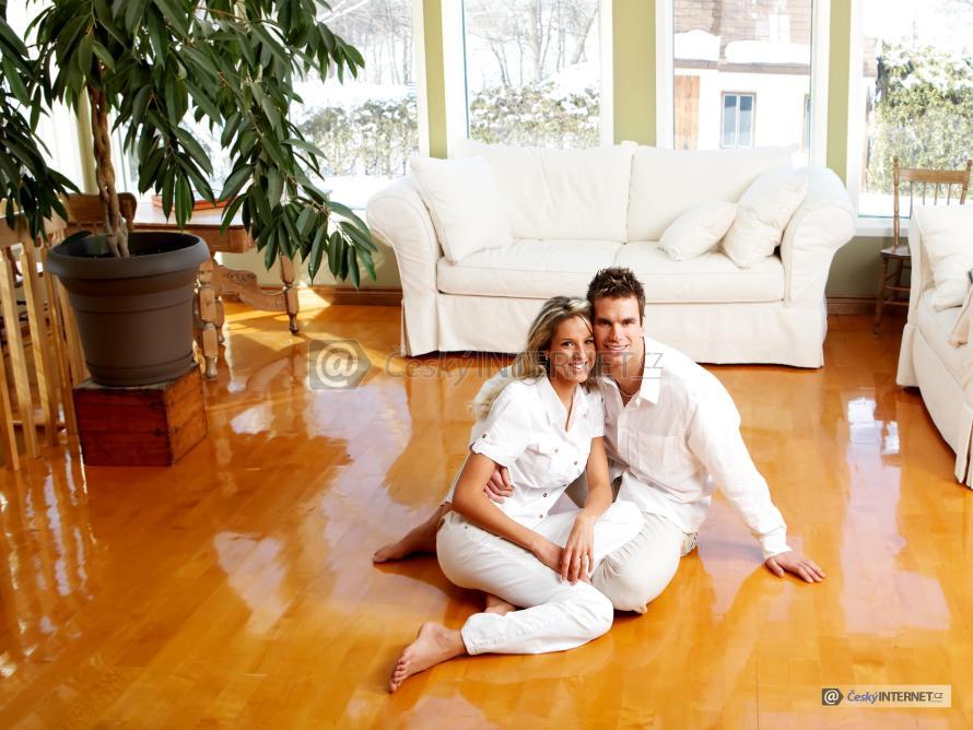Muž se ženou sedí na podlaze v obývacím pokoji.