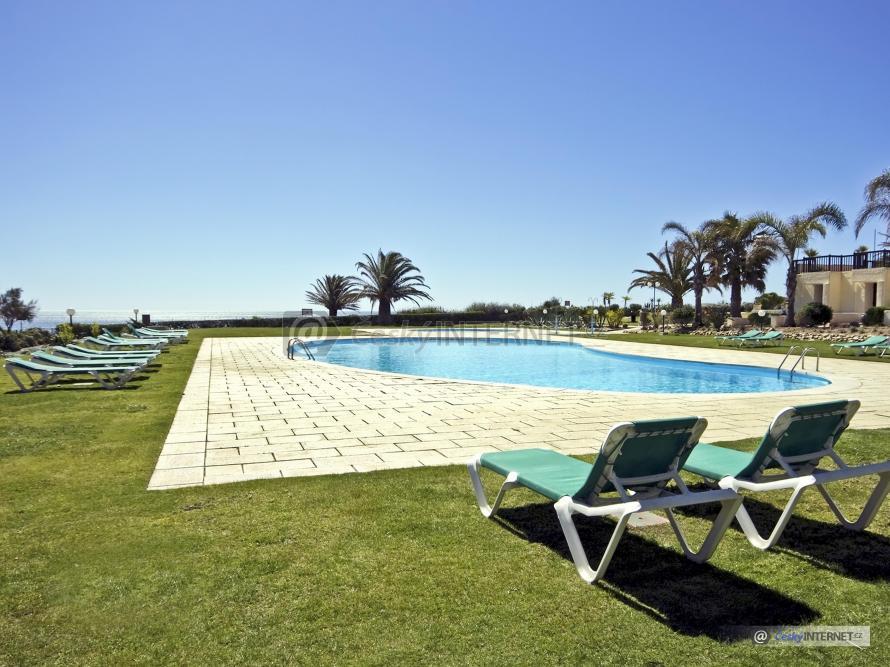 Bazén s terasou a lehátky.