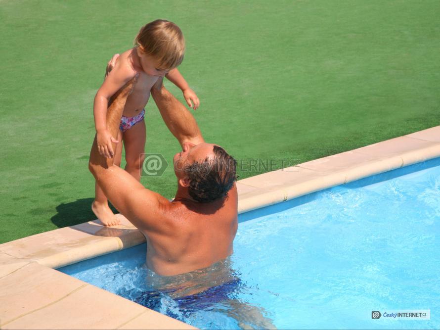 Muž s dítětem v bazénu.