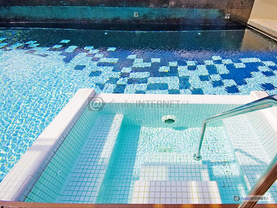 Bazén a vířivka s detailem nerezového zábradlí.