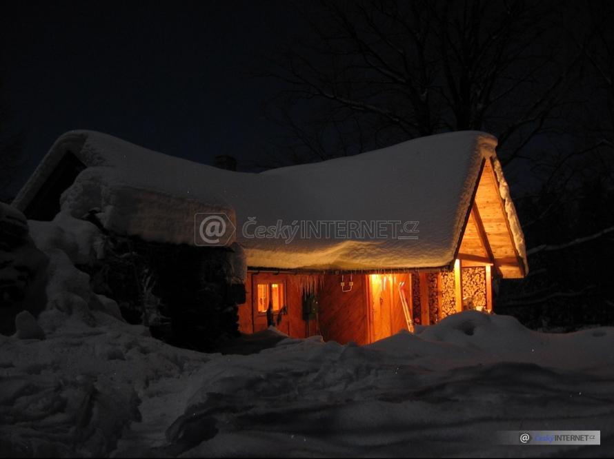 Noční pohled na zasněženou chatu.