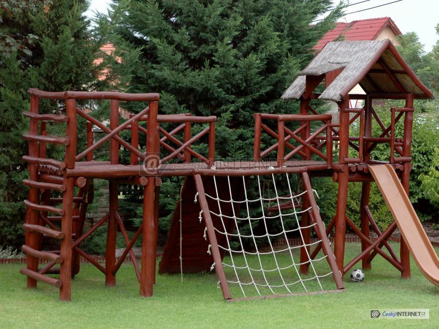 Dřevěné dětské hřiště v zahradě.