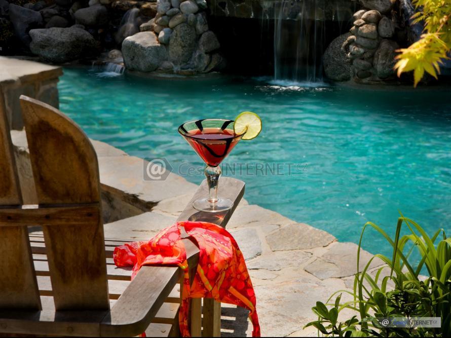 Jezírko s vodopádem v rozkvetlé zahradě.