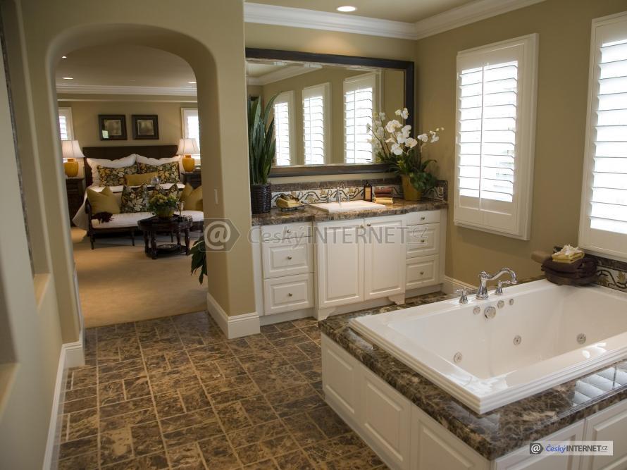 Moderní prostorná koupelna v retro stylu s vířivkou, spojená s obývacím pokojem volným průchodem.