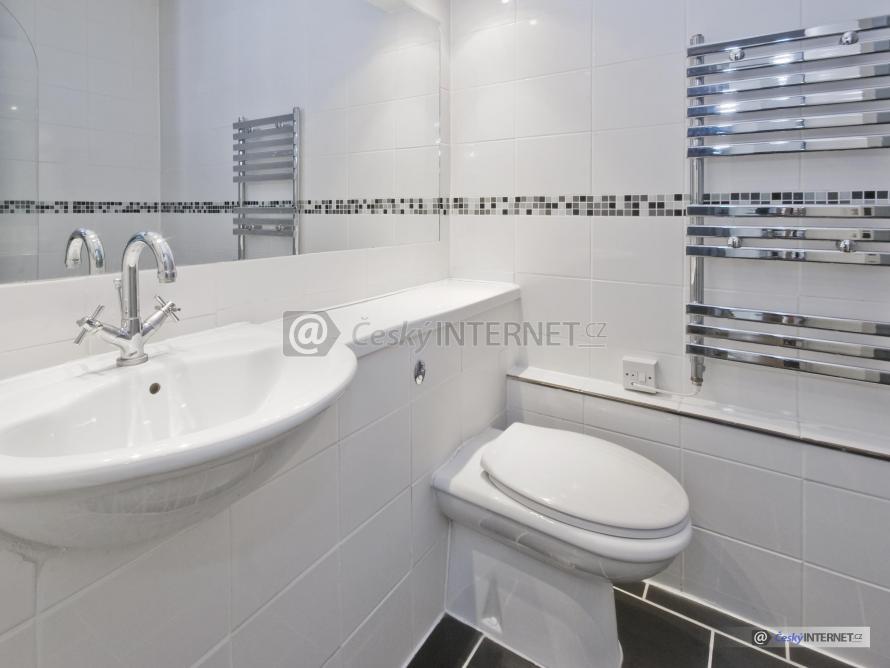 Detail koupelnového zrcadla s umyvadlem, baterií a wc.