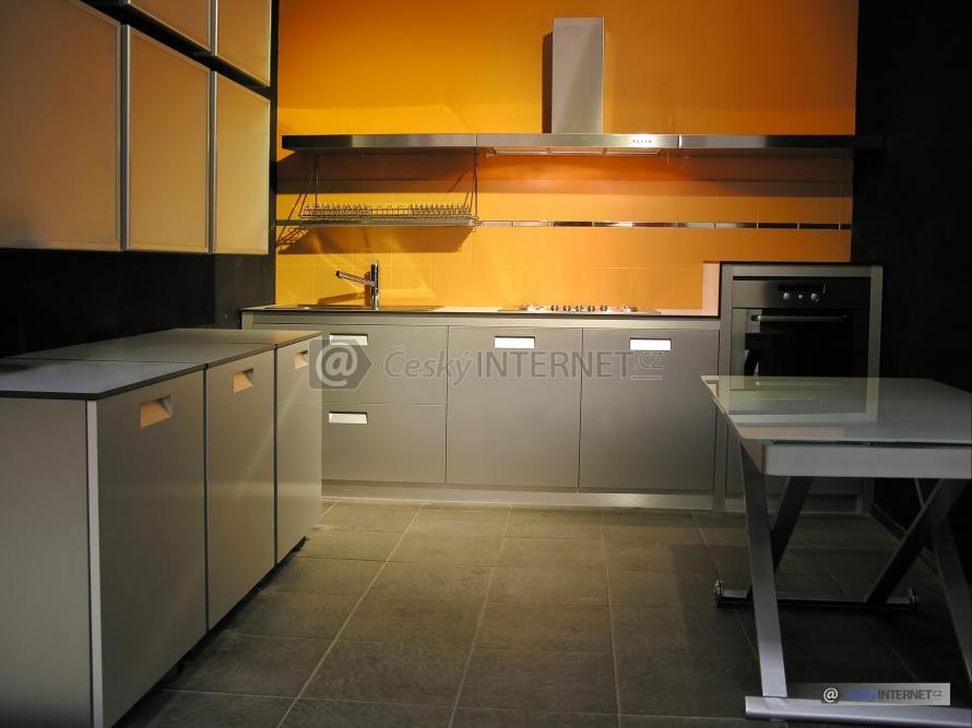 Kuchyně se skleněným jídelním stolkem v popředí.
