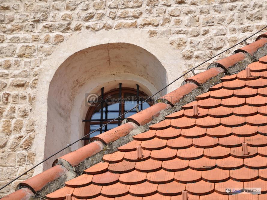 Detail střechy kostela, okna a fasády.