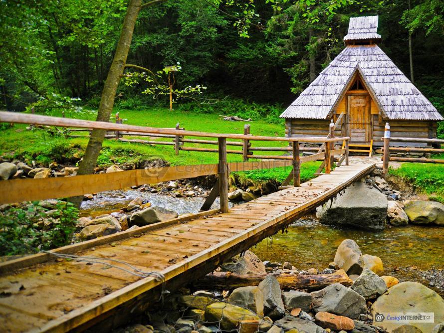 Tradiční roubenka a dřevěná lávka přes potok.