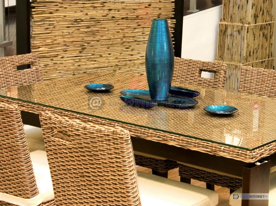Jídelní kout - detail na ratanový stůl se skleněnou deskou, ratanové židle a drobné užité umění  na stole - váza a talířky, mísa.
