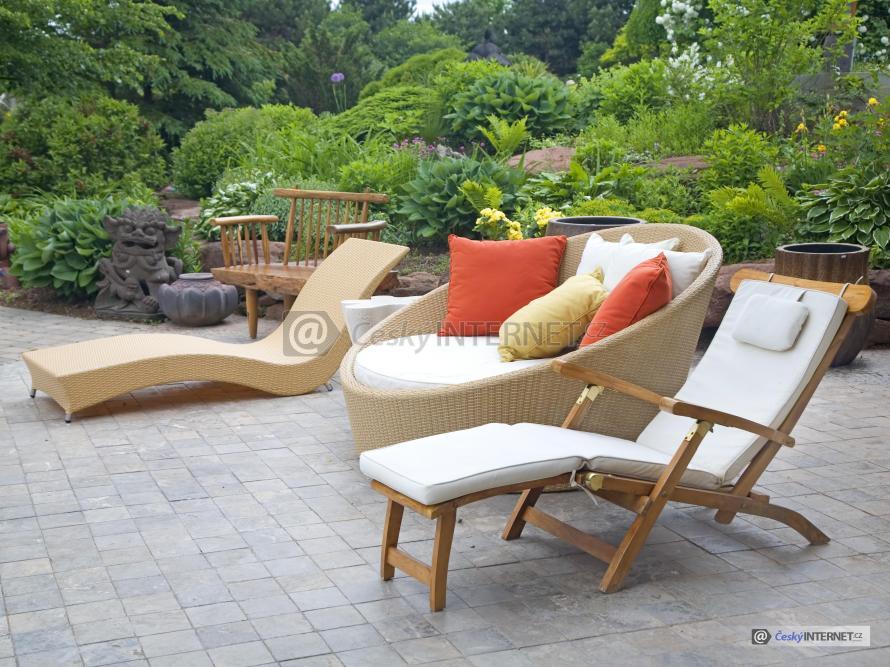 Ratanový nábytek na terase, v pozadí okrasná zahrada.