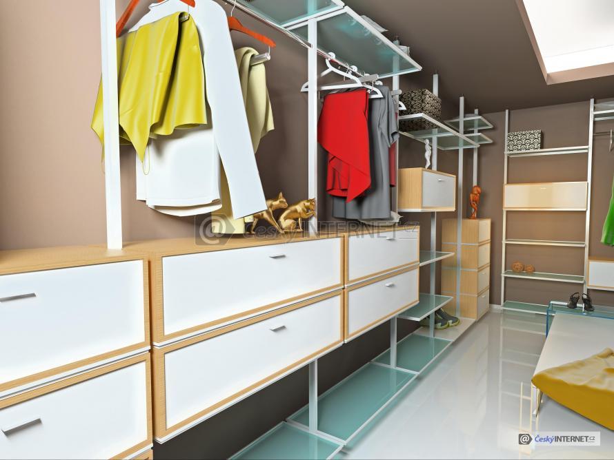 Pohled do prostorné šatny doplněné drobným užitým uměním, ošacení a obuv, lesklá podlaha, jednoduchý a praktický nábytek.