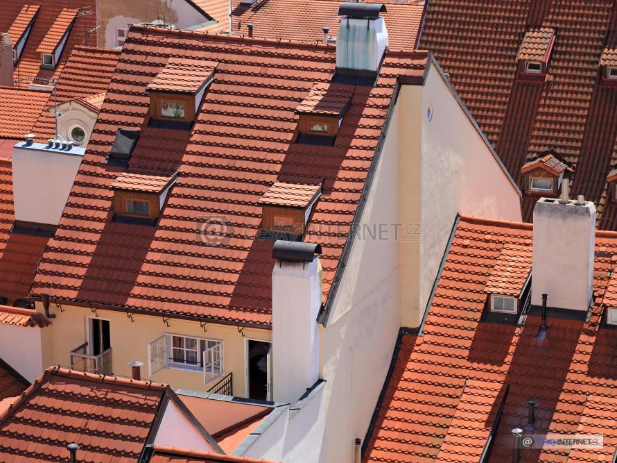 Pohled s výšky na střechy historických domů.