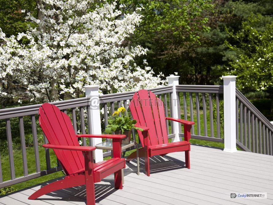 Zahradní křesla na dřevěné terase.