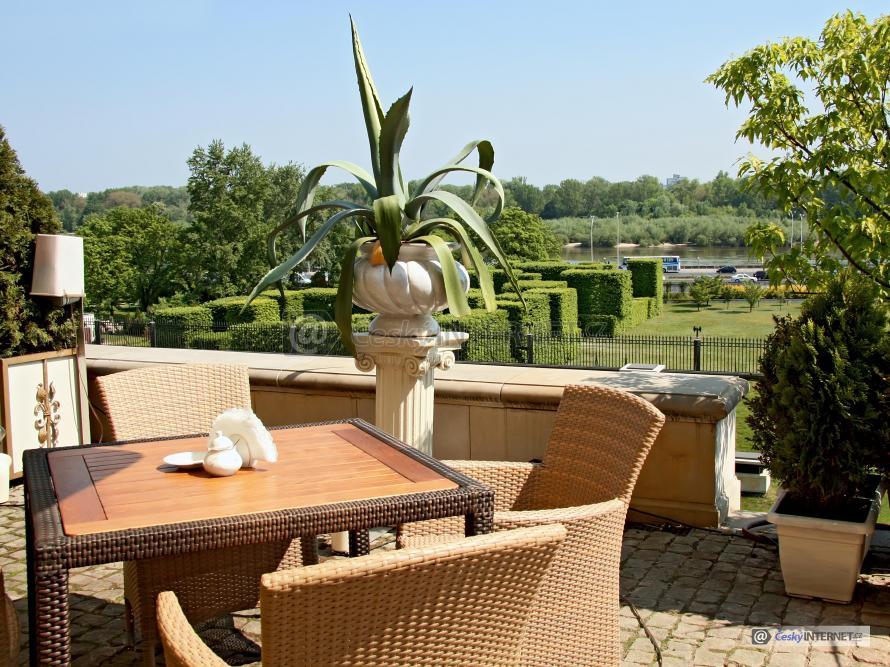 Ratanový nábytek na terase, výhled na zahradu.