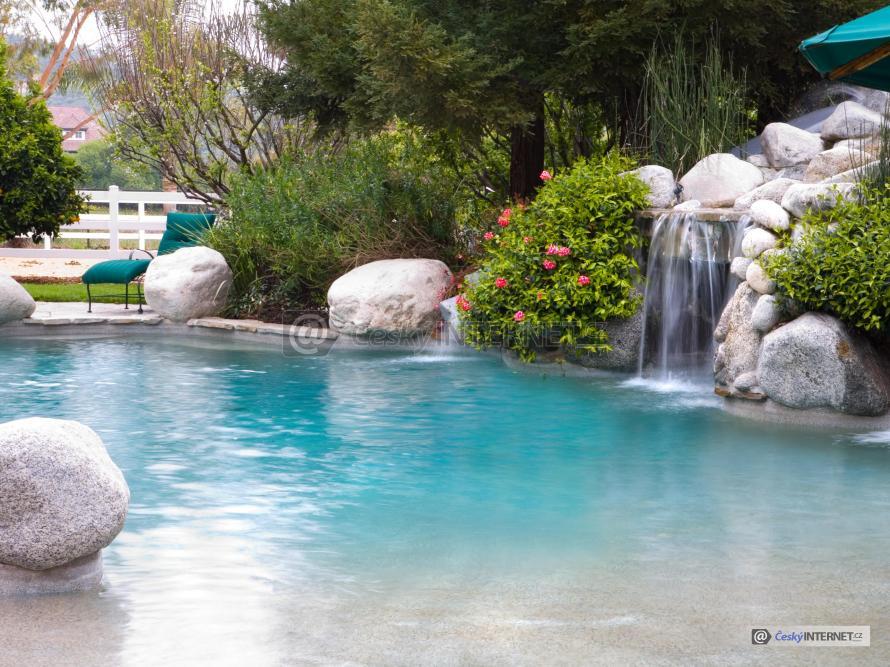 Velké koupací jezírko s vodopádem v rozkvetlé zahradě.