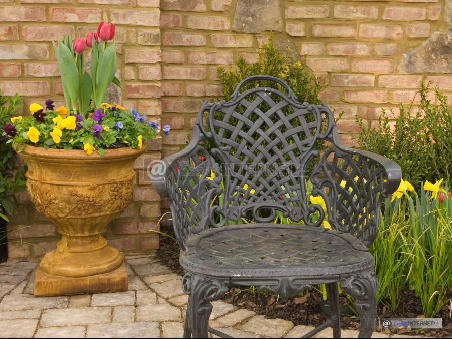 Aranž v okrasné zahradě, kovové křeslo.